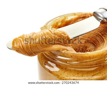 peanut butter spread on a knife and jar - stock photo