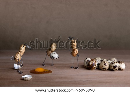 Peanut Easter Bunnies preparing eggs with some small mishaps - stock photo