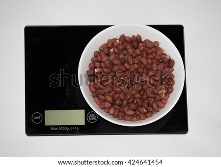 Peanut on a digital white kitchen scale. (weighing products) - stock photo