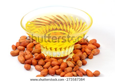 Peanut or groundnut oil in a glass bowl with peanuts or groundnuts isolated on white background - stock photo