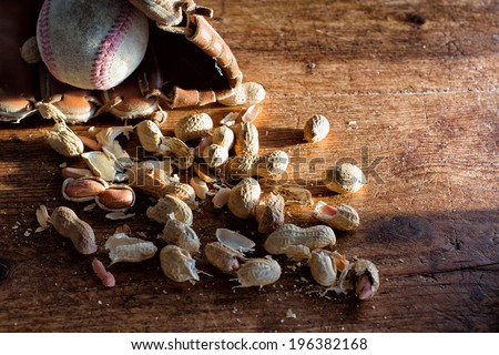 Peanut shells with an old baseball glove and ball on a rustic wood background. Low key with a stream of late afternoon light. Concept for baseball, ballpark, snacks, fans, summer, traditions.  - stock photo