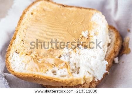 peanuts butter spread on bread slice - stock photo