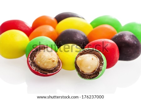 Peanuts covered with chocolate and multicolored candy coatings on a white background
