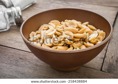 Peanuts in bowl and salt shaker - stock photo