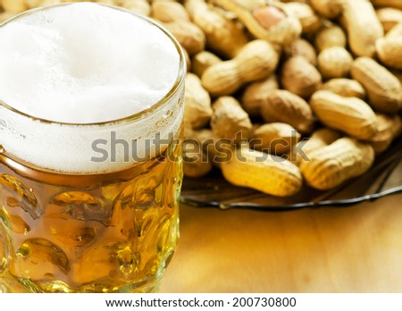 Peanuts in shell with a glass of beer.