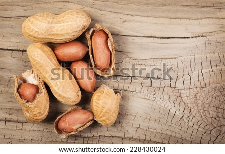 Peanuts in shells on wood background - stock photo