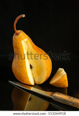 Pear, a knife and a cut  slice  on a black background with reflection