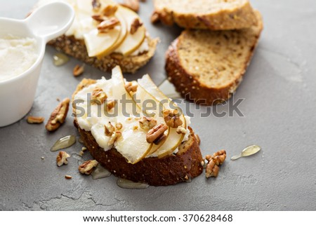 Pear and ricotta bruschetta with nuts and honey - stock photo