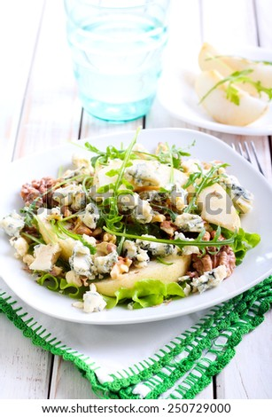 Pear, blue cheese and nut salad on plate - stock photo