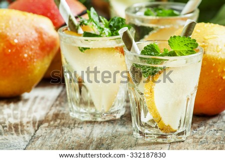 Pear cocktail with soda, fruit slices and mint on an old wooden table, selective focus - stock photo
