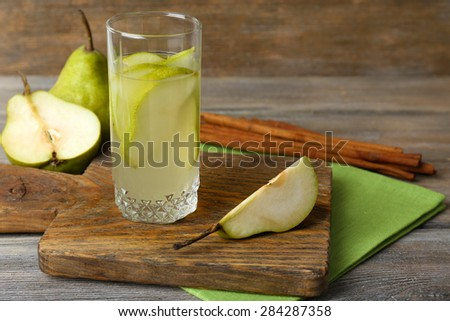 Pear juice with fresh fruits and cinnamon on wooden background - stock photo
