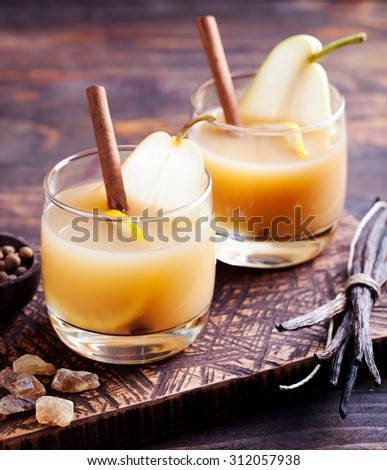 Pear mulled cider with vanilla,lemon slice and cinnamon sticks on a wooden background - stock photo