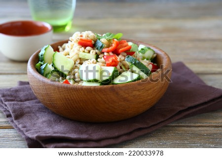 Pearl barley with cucumbers and pepper in a wooden bowl. Salad, healthy food - stock photo