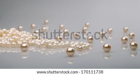 pearl beads and pearls with reflection on gray background - stock photo