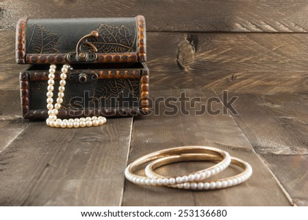 Pearl bracelet and vintage box with jewelry on color wooden background - stock photo