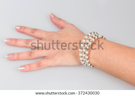 Pearl bracelet on hand at the girl, an ornament of pearls on hand - stock photo