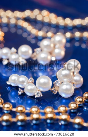 Pearl earring and golden beads on blue background