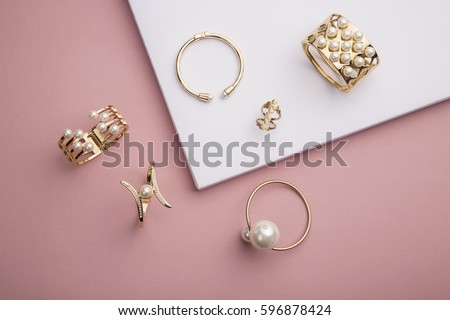 Pearl Golden Bracelets and ring on pink background - Pearl Bracelets on paper background setup