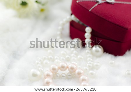 Pearl necklace and bracelet with red jewel box - stock photo