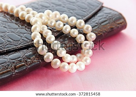 Pearl necklace and leather purse with jewel box on pink background. - stock photo