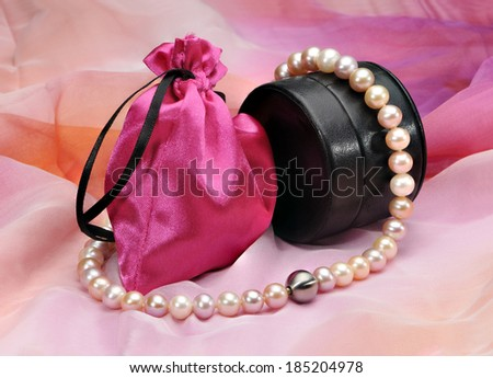 Pearl necklace, black leather case and a pink bag on a colored background.