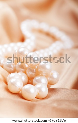 Pearl necklace on the bright satin background - stock photo
