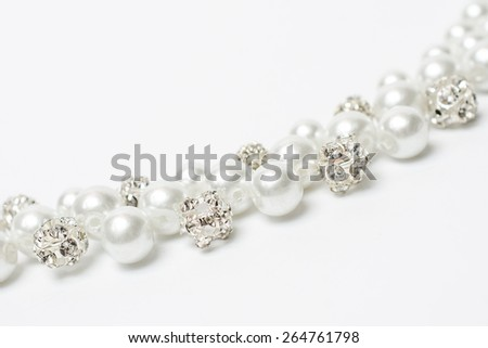 Pearl necklace with diamonds on a white background - stock photo