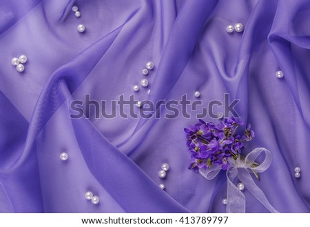 pearls  and bouquet of violets on the blue fabric