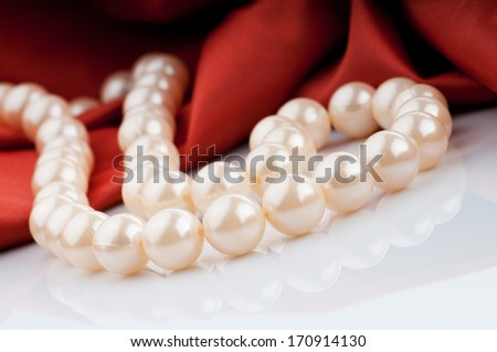 Pearls necklace on satin background