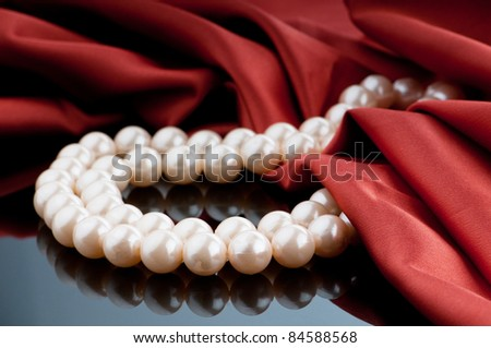 Pearls necklace on satin background - stock photo