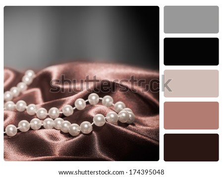 Pearls on a silk fabric colour palette with complimentary swatches. - stock photo