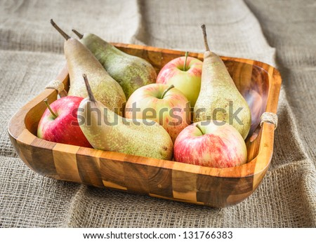 pears and apples in a wooden basket at a jute sack