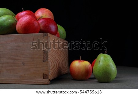 Pears and apples in a wooden box. Fruits on a black background.