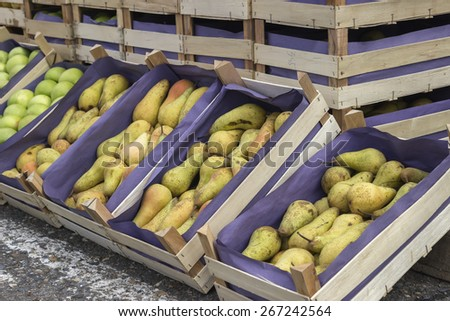 Pears and apples in wooden crates for sale at a street market. selective focus. - stock photo