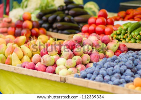 Pears, apples, plums, cucumbers, tomatoes, eggplants in city market - stock photo