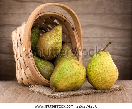 Pears in a basket on wood table - stock photo