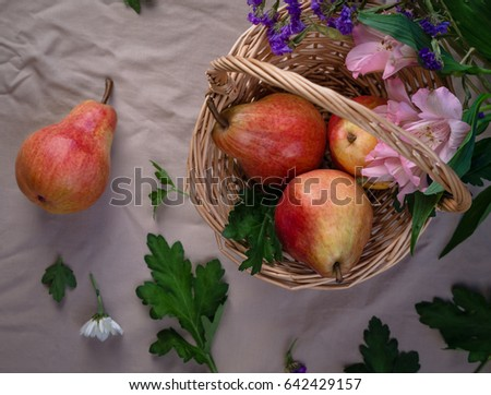 pears in a basket with green leaves and purple and pink flowers with one pear lying outside the basket on a beige cloth