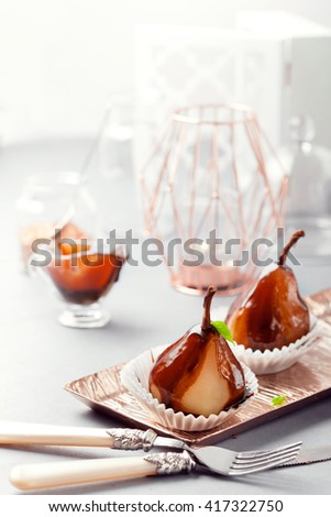 Pears in dark chocolate, sweet dessert set with modern copper colour accessories. Light and contrast photo. Posh and glamour tea time concept.