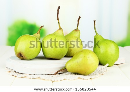 Pears on wooden cutting board, on light background