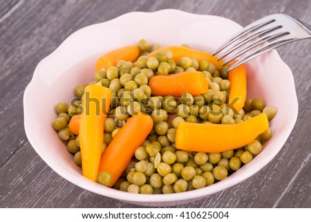 Peas and carrots in bowl isolated on wooden background. - stock photo