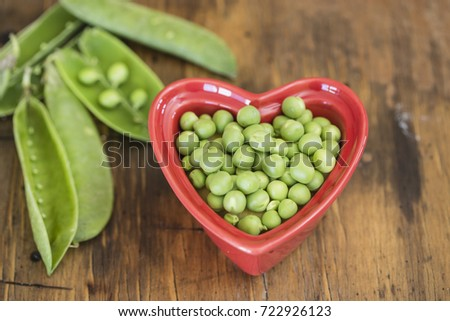 peas in a Red heart shaped bowl and wooden table
