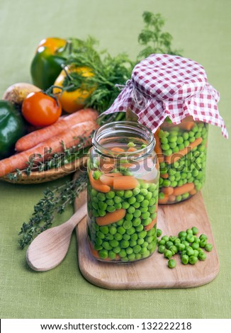 Peas with carrots in glass jar - stock photo