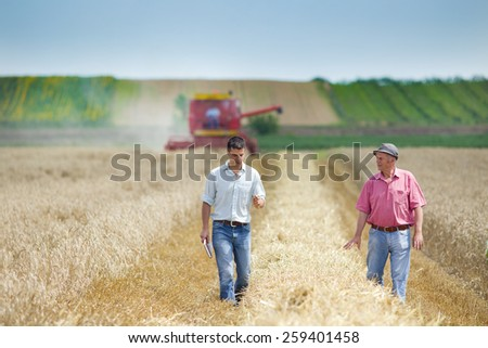 Peasant and business man talking on wheat field during harvesting - stock photo
