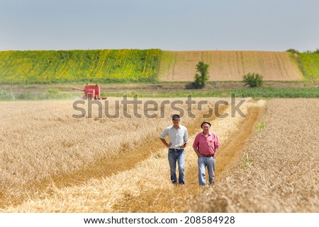 Peasant and business man walking on wheat field during harvesting - stock photo