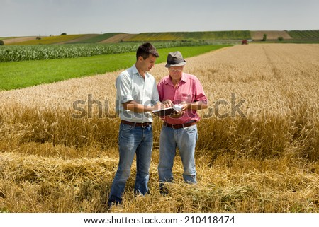 Peasant and businessman looking at notebook on wheat field - stock photo