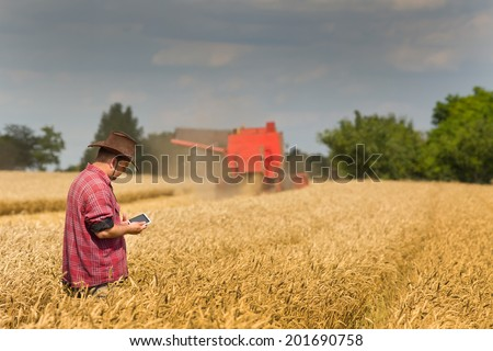 Peasant holding tablet in wheat field with combine in background - stock photo