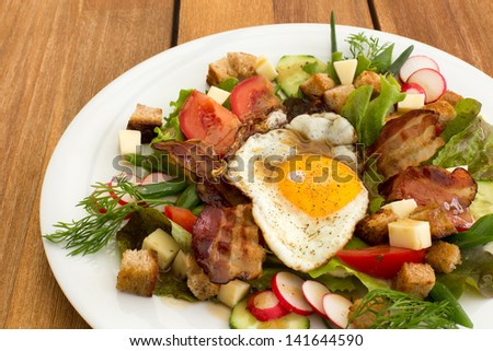Peasant salad also called greek salad, village salad or country salad. Composed with lettuce, cucumber, onion, radish, fried egg and bacon, cheese, tomatoes, parsley and croutons.