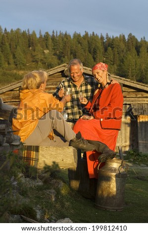 Peasant woman and mature couple having a drink together - stock photo