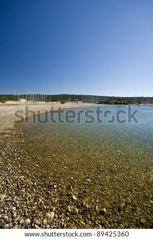 Pebble beach in the Sukosan marina - stock photo