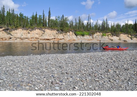Pebble beach North of the river and the boat. Summer landscape of one of the rivers of the Northern slope of the Polar Urals. - stock photo